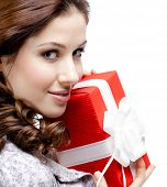 stock photo of gift wrapped  - Young woman hands a gift wrapped in red paper - JPG