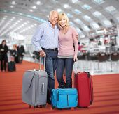 stock photo of carry-on luggage  - Senior couple in airport - JPG