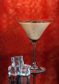 stock photo of bailey  - Baileys liqueur in glass on red background - JPG