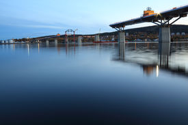 picture of flatboat  - Nightfall bridge construction reaching over water view from beneath - JPG