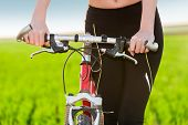 stock photo of riding-crop  - Cropped view of female cyclist with hands on handle bar - JPG