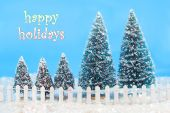 image of winter scene  - Christmas card saying happy holidays with a winter scene in colorful lights on trees bright blue sky a white picket fence and glittering snow - JPG
