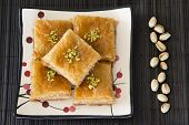 stock photo of baklava  - Baklava on a Plate with Pistachios on a Black Mat