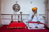 JODHPUR, INDIA - NOVEMBER 26, 2012: Old Indian man smokes hookah (waterpipe) in Mehrangarh fort. The