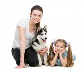 two smiling sisters and a husky dog sitting on the floor on a white background