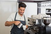 foto of waiter  - Portrait of a young waiter smiling and making cup of coffee at coffee shop - JPG