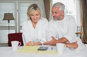 Casual mature couple sitting with home bills and calculator at table