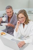 Couple in bathrobes having breakfast while using laptop in the kitchen at home