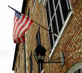 foto of south american flag  - Oil lamp and Amerian Flag hanging from a historic building in South Carolina - JPG