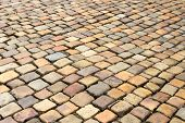 stock photo of pavestone  - Road paved with colored old uneven paving stones