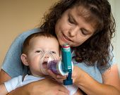stock photo of exhale  - Infant getting breathing treatment from mother while suffering from illness - JPG