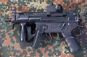 picture of camouflage  - modern 9 mm submachine gun on camouflaged background - JPG