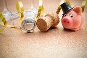 pic of talisman  - Lucky pig and cork from champagne bottle in front of two glasses - JPG
