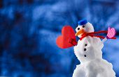 image of top-hat  - Little happy christmas snowman in blue screw top as hat red scarf and with heart love symbol outdoor - JPG