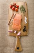 stock photo of tong  - raw salmon fillet tomato thyme sea salt pepper garlic and fishbone tong on wooden board - JPG