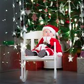 image of santa baby  - Cute Newborn Baby In A Santa Costume And Hat Sitting In A White Rocking Chair Under A Christmas Tree - JPG