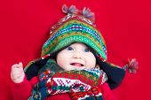 foto of blanket snow  - Funny Baby Girl In A Colorful Knitted Hat And Scarf On A Red Blanket - JPG