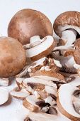 stock photo of agaricus  - Diced and whole agaricus brown button mushrooms also known as portobello as they increase in size ready to be used as a savory cooking ingredient or in vegetarian and vegan cuisine