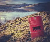foto of hazardous  - Conceptual Image Of A Toxic Waste Barrel Or Drum Near Water In The Countryside - JPG