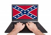 stock photo of flag confederate  - Man working on laptop confederate flag isolated - JPG