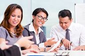 stock photo of southeast asian  - Asian business team brainstorming in project meeting - JPG