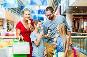 stock photo of mall  - Family eating ice cream in shopping mall with bags - JPG