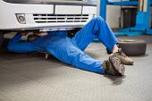 pic of garage  - Mechanic lying and working under car at the repair garage - JPG