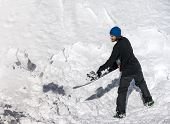pic of snow shovel  - Snowboarder throws snow his snowboard - JPG