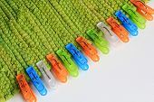 stock photo of pegging  - colorful plastic clothes pegs on green fabric - JPG