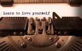 image of typewriter  - Vintage inscription made by old typewriter Learn to love yourself - JPG