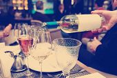 foto of toned  - Waiting is pouring white wine in restaurant - JPG