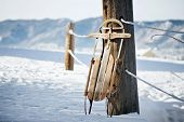 stock photo of sled  - Vintage wood sled leaning on bridge in snowy mountain scene - JPG