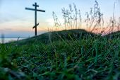 stock photo of cross hill  - cross in sight of the person lying on a grass