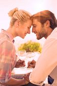stock photo of ponytail  - Happy young couple sitting in the garden enjoying wine together on a sunny day - JPG