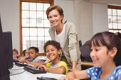 image of classmates  - Cute pupil in computer class with teacher smiling at camera at the elementary school - JPG