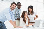 stock photo of coworkers  - Happy coworkers working together with laptop in the office - JPG