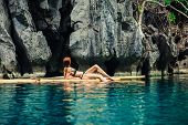 picture of raft  - A beautiful young woman in a swimsuit is relaxing on a bamboo raft in a tropical lagoon - JPG