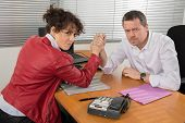 image of wrestling  - Man and woman in arm wrestling gesture on working table during meeting  - JPG