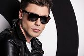 pic of jacket  - Handsome male model in leather jacket standing against target background and looking at camera - JPG