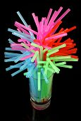 stock photo of water shortage  - Long drink glass with some water and many colored plastic straws symbolizing upcoming  global water shortage - JPG