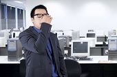 stock photo of forehead  - Young asian businessperson having problem and massaging his forehead in the office - JPG