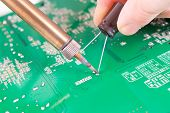 picture of capacitor  - Serviceman soldering capacitor on PCB with soldering iron in the service workshop - JPG