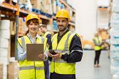 foto of warehouse  - Warehouse manager talking with worker in a large warehouse - JPG
