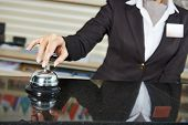 stock photo of receptionist  - female receptionist worker ringing at hotel counter bell - JPG