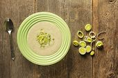 picture of leek  - Top view of a bowl of leek soup with fresh leek rings on a wooden background - JPG