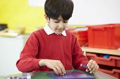 picture of math  - Male Pupil Practising Maths At Desk - JPG