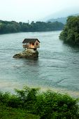 stock photo of hazy  - House on a rock on a hazy river Drina in Serbia - JPG