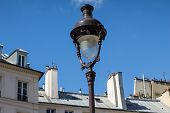 stock photo of lamp post  - A lamp-post over rooftops of Parisian buildings ** Note: Shallow depth of field - JPG