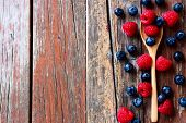 pic of spoon  - Top view of Berries with spoon on Rustic Wooden Background - JPG