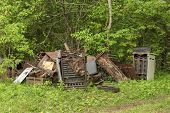 foto of dump  - A bunch of scrap metal old household appliances dumped at the edge of a wood - JPG